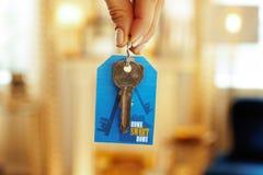 Primo piano sulle chiavi della porta con l'etichetta a disposizione della donna moderna immagine stock libera da diritti