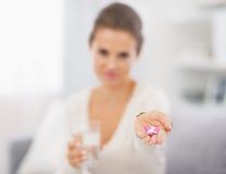 Primo piano sulle pillole a disposizione della giovane donna immagine stock