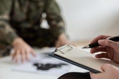 Primo piano sullo psicoterapeuta che prende le note mentre analizzando comportamento del soldato nel corso della riunione immagini stock