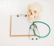 Primo piano sullo stetoscopio e sulla lavagna per appunti umani del cranio Fotografia Stock