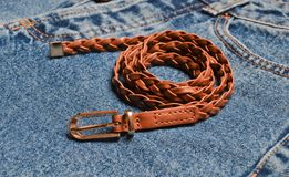 Primo piano tessuto Brown della cinghia di cuoio sulle blue jeans Immagine Stock