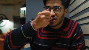 Primo piano, tipo indiano con i vetri che mangia il dolce di cioccolato al caffè video d archivio