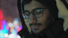 Primo piano, tipo triste negli sguardi del cappuccio alla candela bruciante riflessa in vetri stock footage