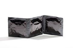 Primo piano tre pacchetti dei preservativi che stanno sulla superficie di bianco che affronta macchina fotografica, plastica d'im Fotografie Stock Libere da Diritti