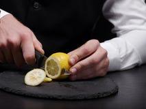 Primo piano un barista che taglia un limone Un uomo che affetta limone giallo su un fondo nero Frullato della frutta che fa conce fotografie stock