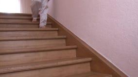 Primo piano un uomo in pantaloni bianchi che cammina giù il punto di legno al primo piano nella casa archivi video