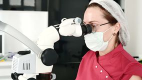 Primo piano una donna in vetri con un dentista professionista che lavora con un microscopio stomatologico professionale in lei stock footage