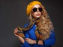 Primo piano una ragazza in un berretto giallo ed in una posa d'uso degli occhiali da sole Fotografie Stock Libere da Diritti