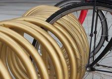 Primo piano urbano dello scaffale del cerchio del supporto dorato della bicicletta Fotografia Stock