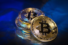Primo piano virtuale dorato dei fondi Bitcoins della foto nuovo su un fondo blu Fotografie Stock Libere da Diritti