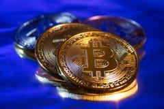 Primo piano virtuale dorato dei fondi Bitcoins della foto nuovo su un fondo blu Fotografia Stock