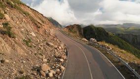 Primo piano volante basso di vista aerea su un paesaggio con una serpentina della strada asfaltata della montagna in una gola pro stock footage