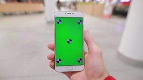 primo punto di vista della persona, facendo uso dello schermo verde in bianco dello smartphone in un centro commerciale, modello archivi video