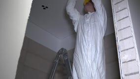 Primo punto nell'installazione della luce ecologica nel soffitto elettricista - tagliare foro video d archivio