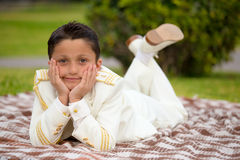 Primo ragazzo di comunione dei giovani che si trova su una coperta sopra l'erba Fotografia Stock