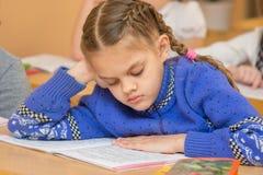 Primo selezionatore al testo della lettura di lezione della lettura che si siede ad uno scrittorio della scuola Fotografia Stock Libera da Diritti