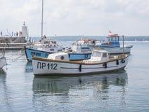PRIMORSKO, BULGÁRIA - 26 DE AGOSTO DE 2011: Porto de Primorsko - barcos de pesca no primeiro plano, no farol pequeno e em turista Imagem de Stock