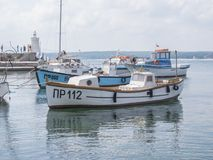 PRIMORSKO, BULGARIJE - AUGUSTUS 26, 2011: Haven van Primorsko - vissersboten in de voorgrond, de kleine vuurtoren en de toeristen Stock Afbeelding