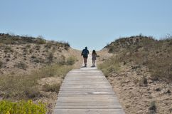 Couple walking on boardwalk toward sea beach stock photos