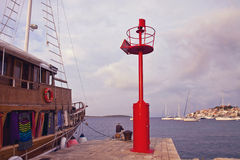 Primosten, Croatia -  fisher and boat at pier with view of the c Stock Photos
