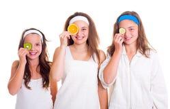 Primping flickor som har gyckel med fruktskivor Royaltyfri Foto