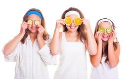 Primping flickor som har gyckel med fruktskivor Arkivbild