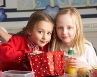Primärschule-Schüler, die das gepackte Mittagessen in Cla genießen Stockbilder