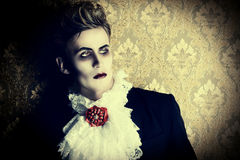 Prince vampire. Portrait of a handsome male vampire over vintage background. Halloween. Dracula costume Royalty Free Stock Images