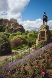 Princes street gardens and the statue of Thomas Guthrie with Edinburgh Castle visible in the background on a beautiful sunny day royalty free stock image