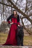 Princesa bonita no vestido vermelho e no revestimento preto da pele que levantam na coroa junto com seu cão em Forest During Earl imagens de stock