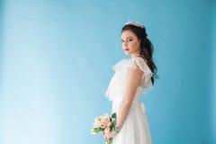 Princesa Bride en un vestido blanco con una corona en un fondo azul Foto de archivo