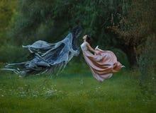 A princesa delgada nova com cabelo escuro e corte de cabelo puro vestiu uma dança de voo de vibração luxuoso longa do vestido no  fotos de stock