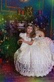 Princesa joven en un vestido blanco con una tiara en su cabeza en el árbol de navidad Fotografía de archivo libre de regalías