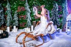 A princesa pequena bonito em um vestido branco senta-se em um trenó e os lances nevam acima imagem de stock