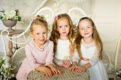 A princesa três pequena senta-se em torno da tabela Imagens de Stock Royalty Free