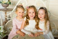 A princesa três pequena senta-se em torno da tabela Fotos de Stock Royalty Free