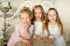 A princesa três pequena senta-se em torno da tabela Fotos de Stock