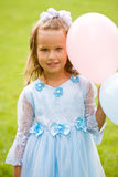 Princess. Portrait of little girl in blue dress on the green grass with balloons Royalty Free Stock Photography