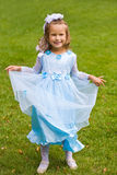 Princess. Portrait of little girl in blue dress on the green grass Royalty Free Stock Photography