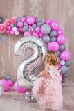 Princess baby girl celebrating life event wearing golden crown and pink airy dress. Cute girl posing in pastel colors studio shoot stock photos