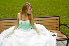 Princess on Bench with Frog. Princess sitting on a bench with a frog beside her Royalty Free Stock Photo