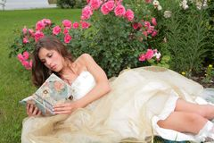 Princess with book in hand in the flowers Stock Images