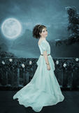 Princess Budur. The little girl in a long dress in oriental ornaments on the balcony on the background of the river under the moon Royalty Free Stock Images