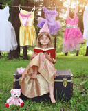 Princess Child Reading Story Book with Glasses. A little girl is sitting outside wearing a princess costume reading a story book with glasses on for an education stock photo