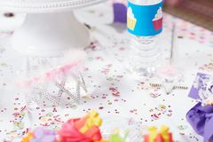 Princess crown at a birthday party for children. Close-up of a toy princess crown and wand on a table with colorful confetti at a birthday party for children Stock Photos