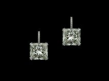 Princess diamonds earrings. A pair of princess square diamonds earrings on black background Royalty Free Stock Photography