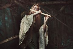 Princess of the elves playing flute Royalty Free Stock Image