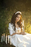 Princess in the forest. Lovely young woman bride in a long white wedding dress billowing in the beautiful summer garden Stock Images
