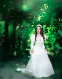 Princess in the forest. Lovely young woman bride in a long white wedding dress billowing in the beautiful summer garden Royalty Free Stock Images