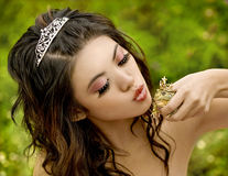 Princess and the Frog. Beautiful princess about to kiss her frog prince Royalty Free Stock Photography